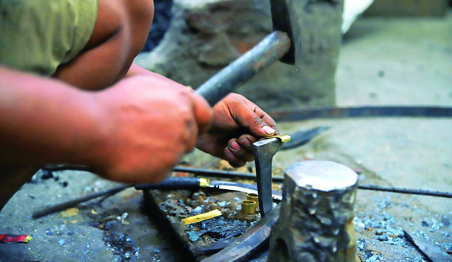 forging a brass holder to perfectly fit inside the handle of a khukuri.